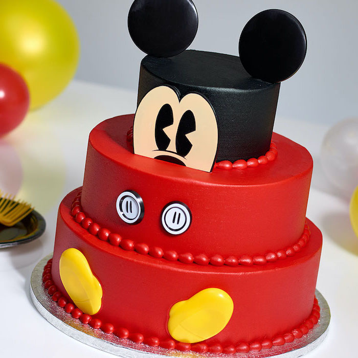 mickey mouse cake, three tier cake, covered with black and red fondant, placed on a silver cake tray