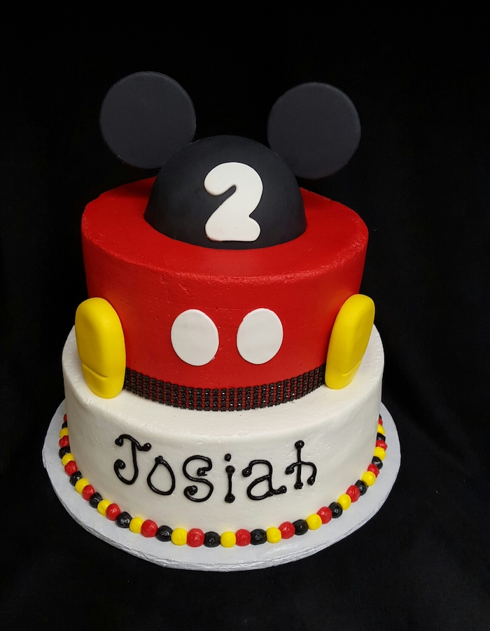 two tier cake, covered with black red and white fondant, decorated with fondant, celebration cakes, placed on white tray