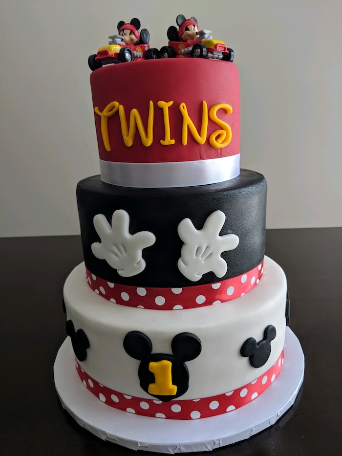 three tier cake, covered with red black and white fondant, mickey mouse cake, decorated with two cake toppers