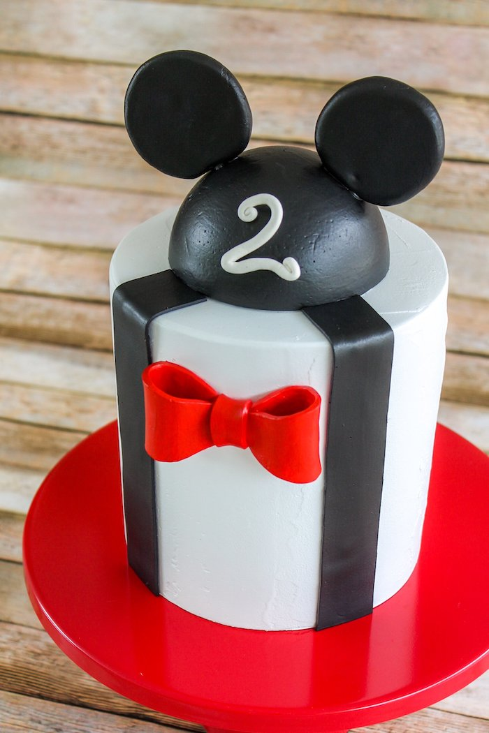 one tier cake, covered with white fondant, decorated with black and red fondant, mickey mouse cake, placed on red cake stand