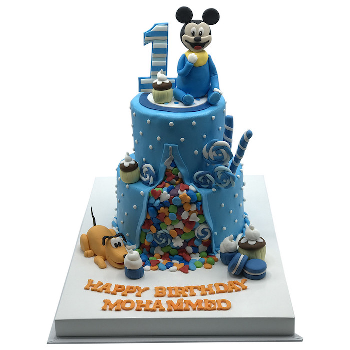 two tier cake, covered with blue fondant, mickey mouse birthday cake, fondant candy spilling out of the cake