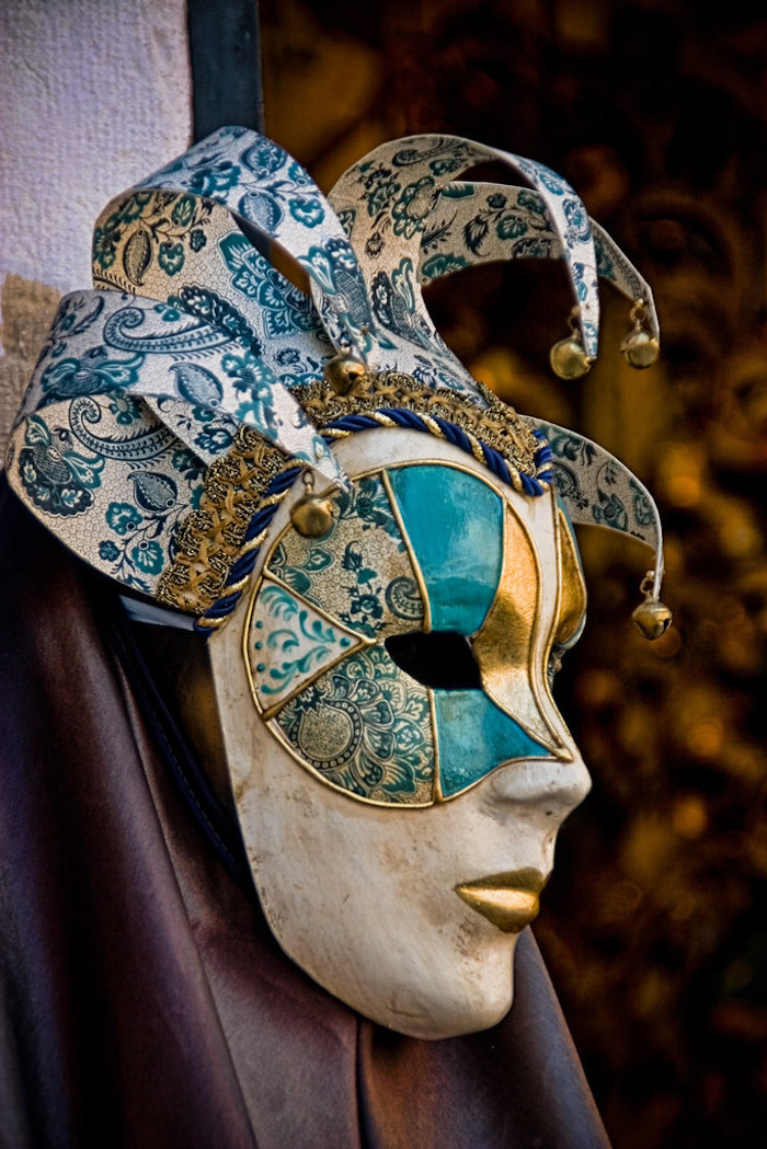 black masquerade mask, white mask decorated in gold and blue, lips painted in gold, bells at the end