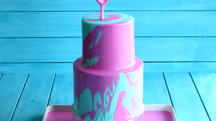 two tier cake, covered with blue and pink glaze, mirror glaze, placed on blue wooden background