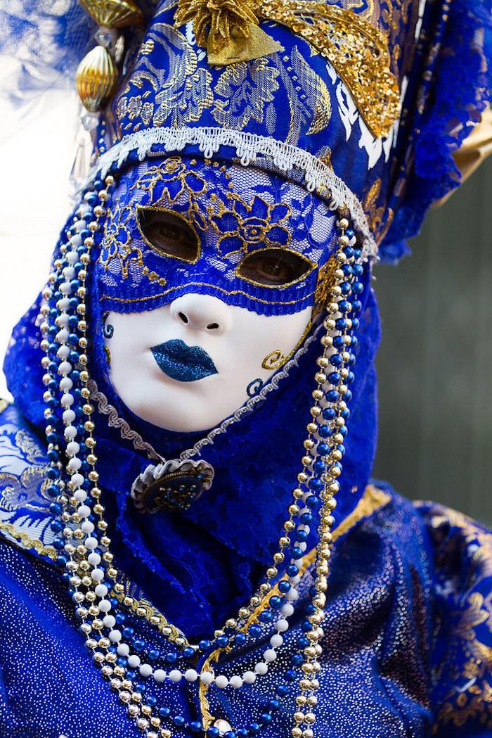 blue white and gold mask, mardi gras mask, decorated with blue and gold lace, blue and gold beads around it