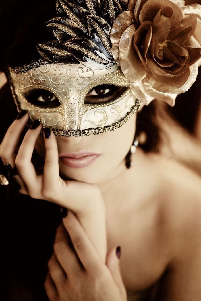 woman wearing gold mask, decorated with glitter, plastic rose on the side, black masquerade mask