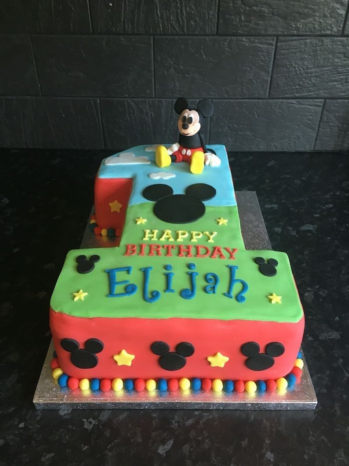 cake in the shape of the number one, mickey mouse 1st birthday cake, covered with blue green and red fondant