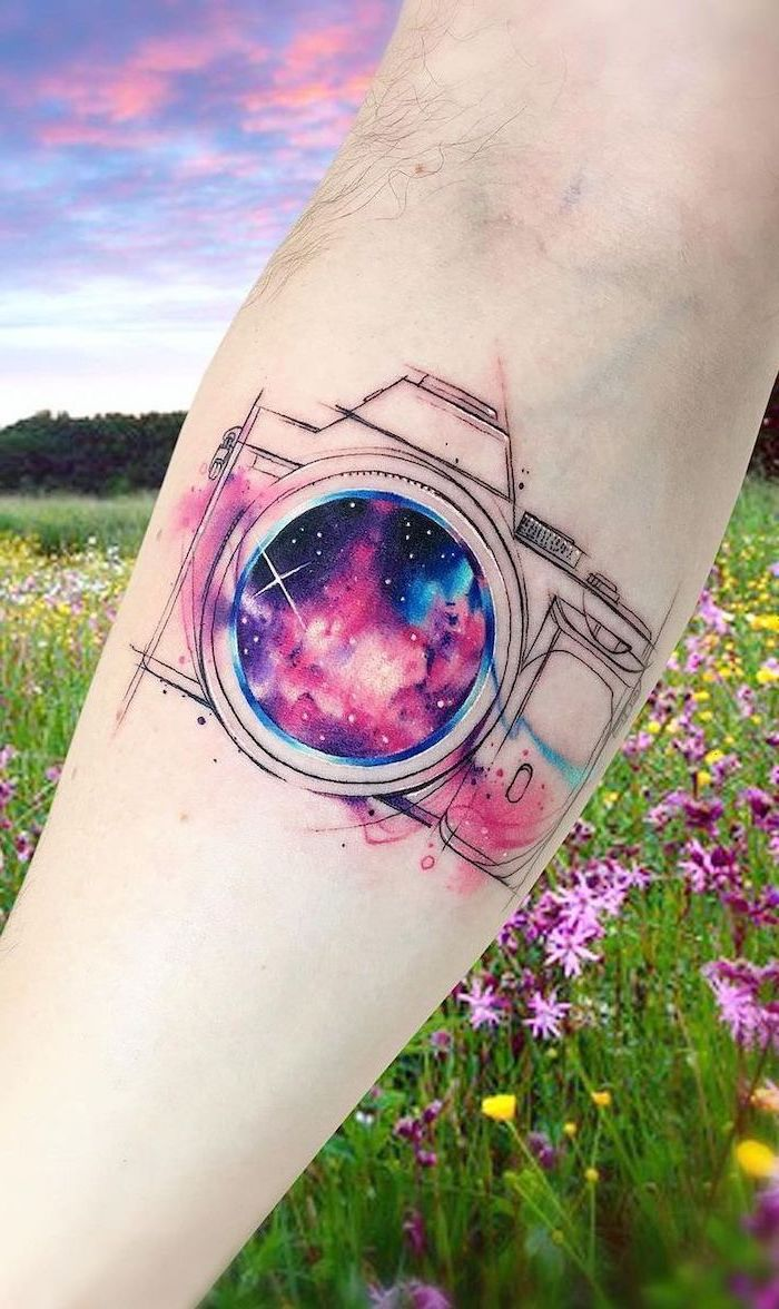 photo camera forearm tattoo, camera lens with galaxy inside, universe tattoo, black purple and pink colors