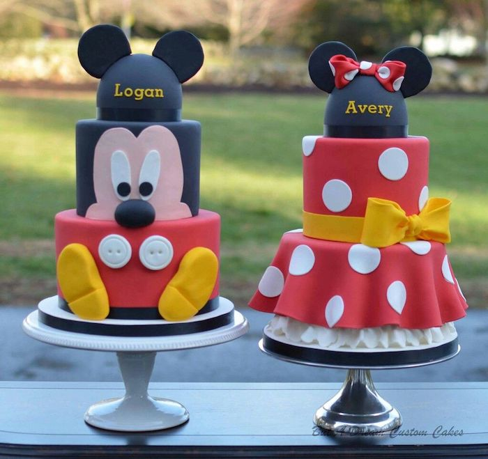 two three tier cakes, covered with black white and red fondant, mickey mouse 1st birthday cake, placed on white cake stands
