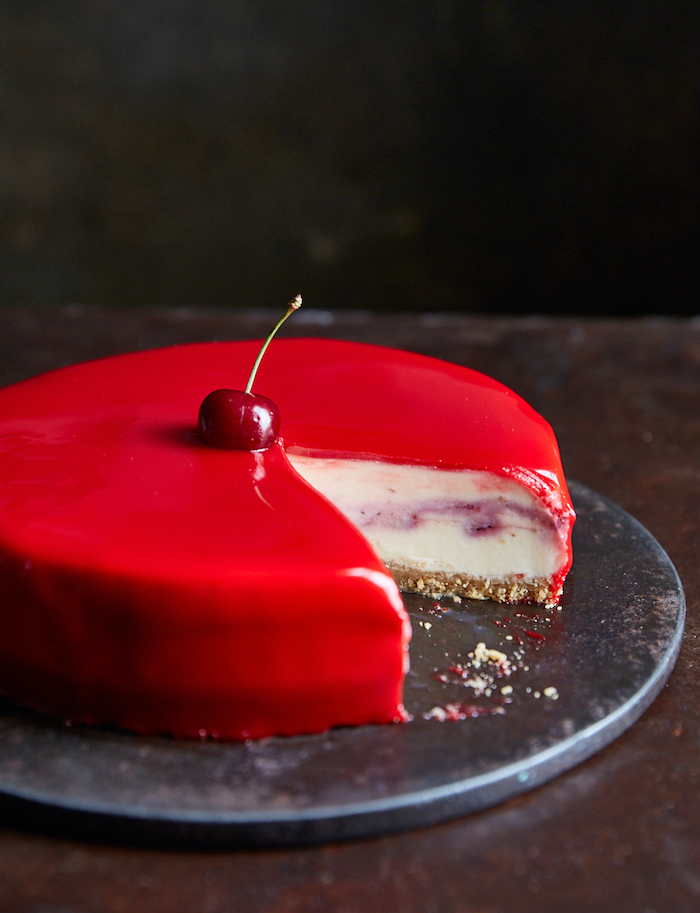 cherry white chocolate cheesecake, covered with red glaze, two tier cake, cherry on top, placed on metal cake tray