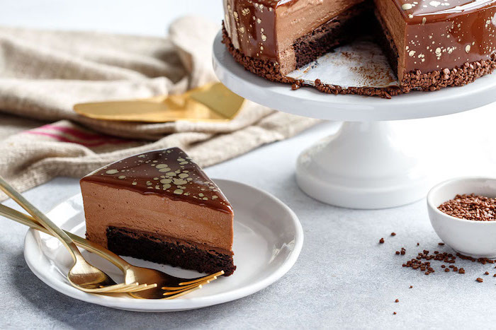 slice of chocolate mousse cake, covered with chocolate gold glaze, two tier cake, placed on white plate with brass forks