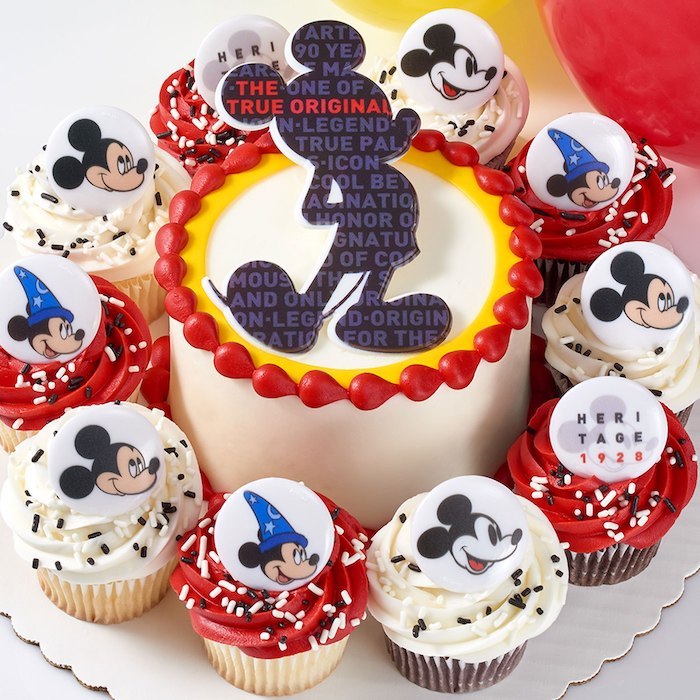one tier cake, covered with white fondant, mickey mouse 1st birthday cake, cupcakes arranged around it