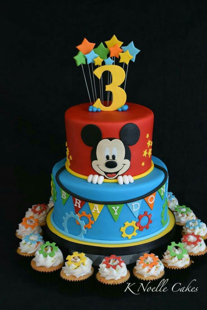 mickey mouse cake ideas, two tier cake, covered with red and blue fondant, cupcakes arranged around it