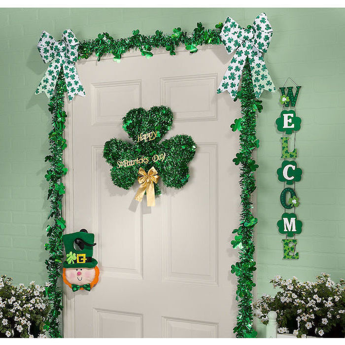 white wooden door, st patricks day wreath, decorated with green garland, two green and white ribbons in the corners