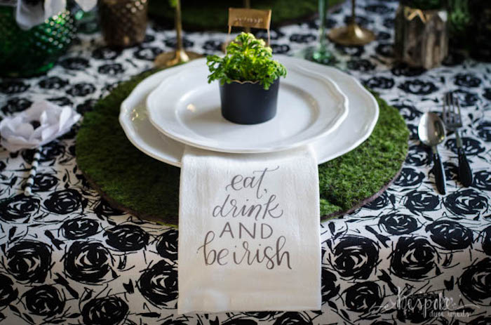 eat drink and be irish napkin, st patrick's day wreath, moss place mat, two white plates, small plant on them