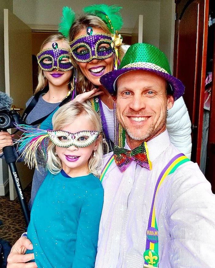 family man and woman with their two daughters, black masquerade mask, wearing masks and hats in purple gold and green