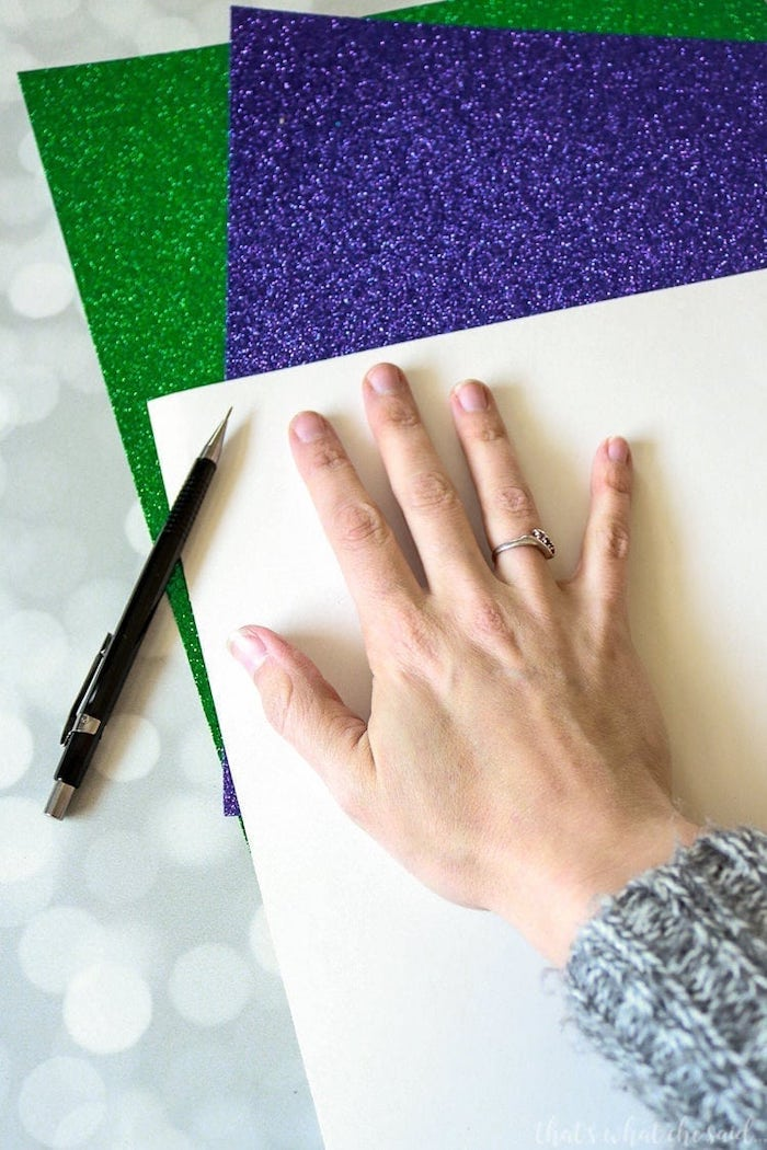 purple and green glitter paper, masquerade ball masks, female hand placed on a sheet of paper, to be traced with pencil
