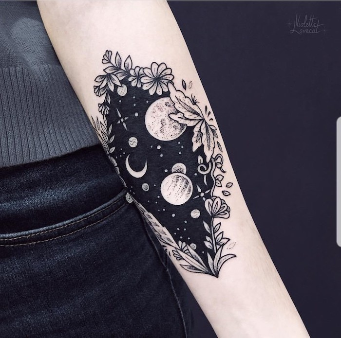 black and white forearm tattoo, universe tattoo, galaxy with planets and stars inside a floral frame