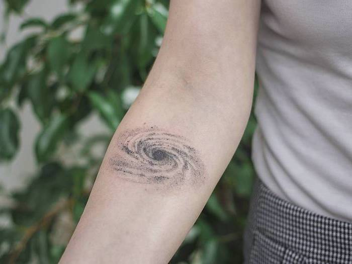 milky way galaxy, forearm tattoo, outer space tattoo, woman wearing grey top