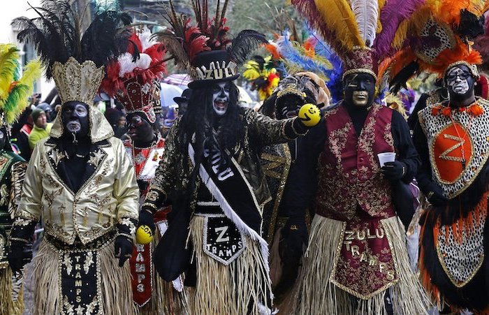 four men dressed in different costumes, wearing large hats with colorful feathers, gold masquerade mask