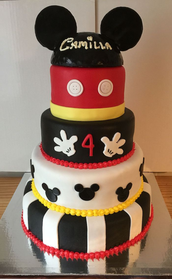 mickey cake, five tier cake, covered with white and black, yellow and red fondant, placed on silver cake tray