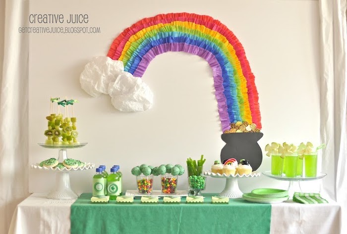 fringe crepe paper rainbow, hanging on white wall, st patricks day wreath, over a desserts table with drinks and candy