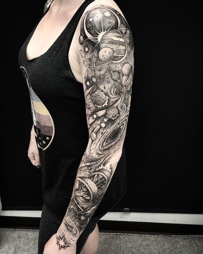 whole sleeve tattoo, planets galaxies and stars, woman wearing black top and pants, galaxy tattoo sleeve