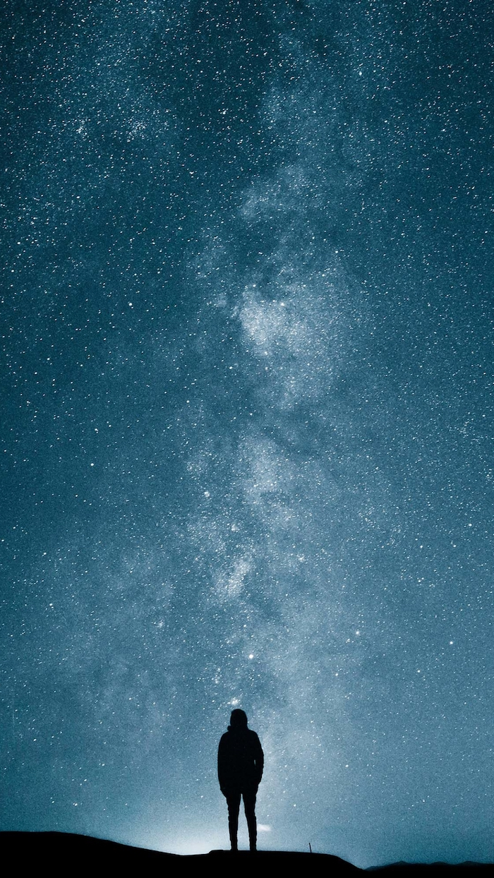 man standing on top of a hill, space wallpaper iphone, blue and white sky, filled with stars