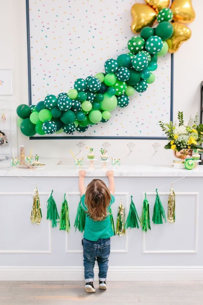 green and gold balloon hanging on white wall, st patricks day wreath, over a desserts table, green and gold tassel garland