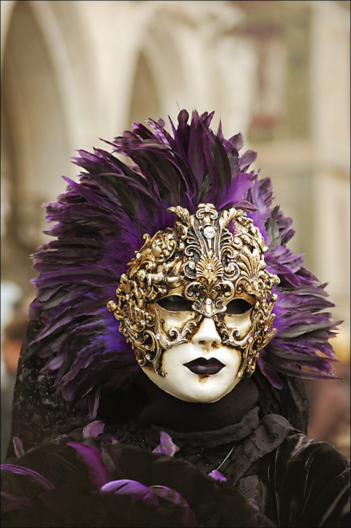 woman wearing white and gold mask, decorated with large black and purple feathers, gold masquerade mask