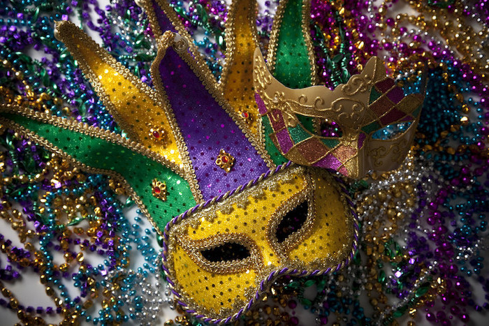two masks in gold purple and green, decorated with glitter and rhinestones, masquerade masks for men, lots of beads necklaces