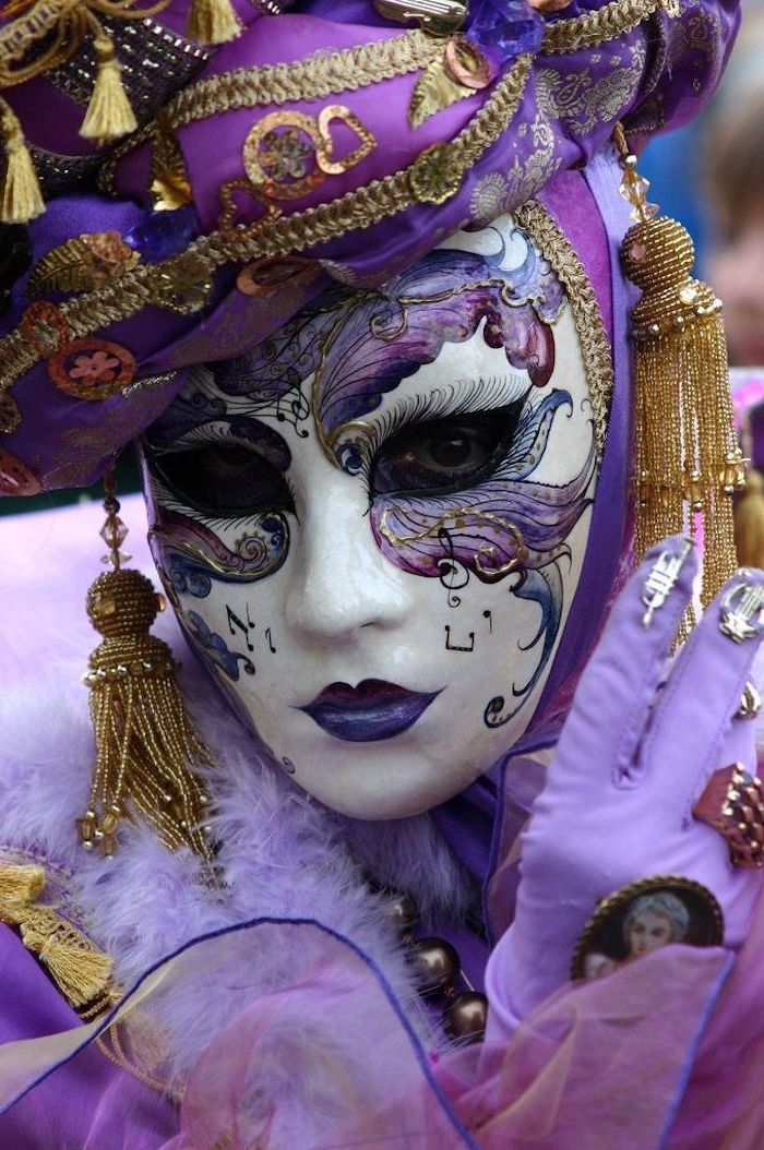 woman dressed in purple and gold costume, masquerade masks for men, mask with purple decorations painted on it