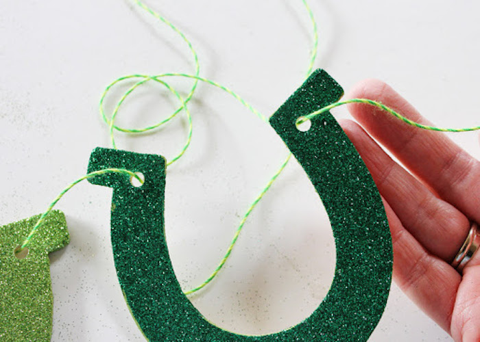 green glitter horseshoe, held together by green and yellow thread, st patrick's day crafts, step by step diy tutorial