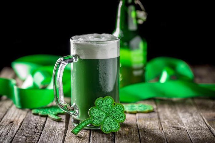 green ber in a mug, placed on wooden table, st paddy's day, glitter shamrock decorations around it