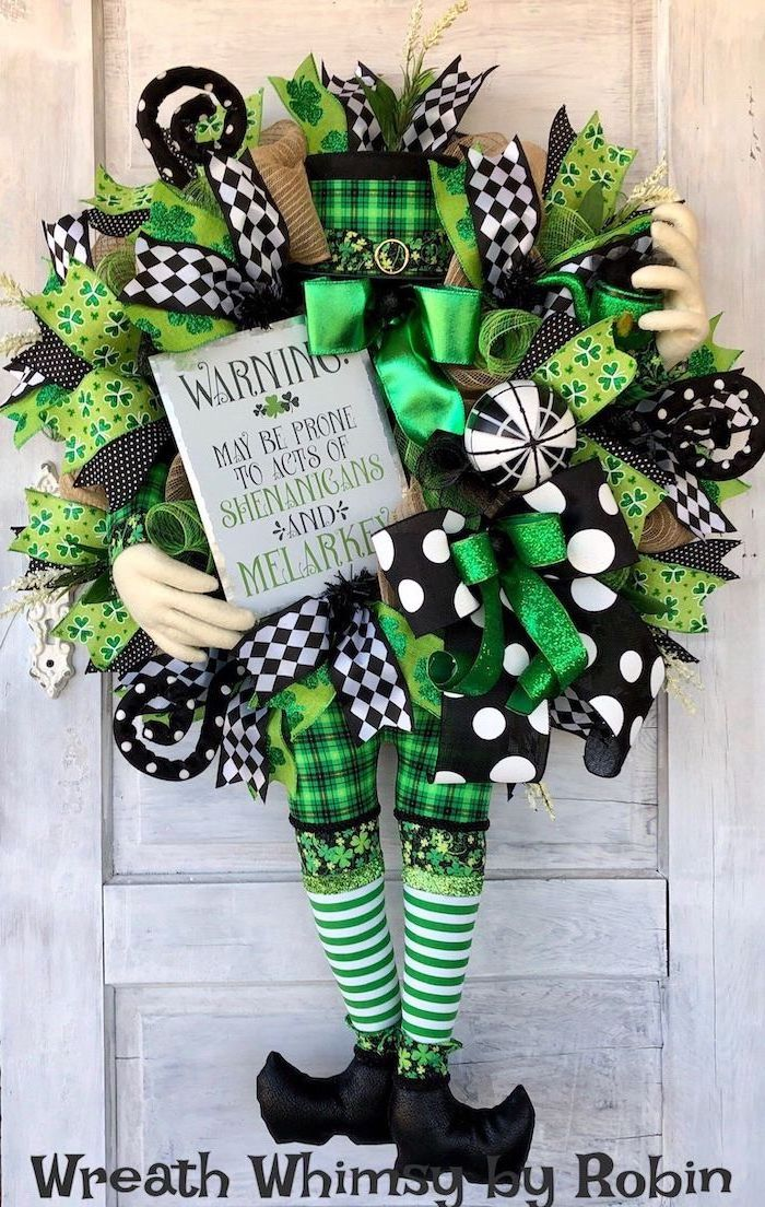 wreath made with different ribbons, green gold black and white, hanging on white wooden door, st patrick's day accessories