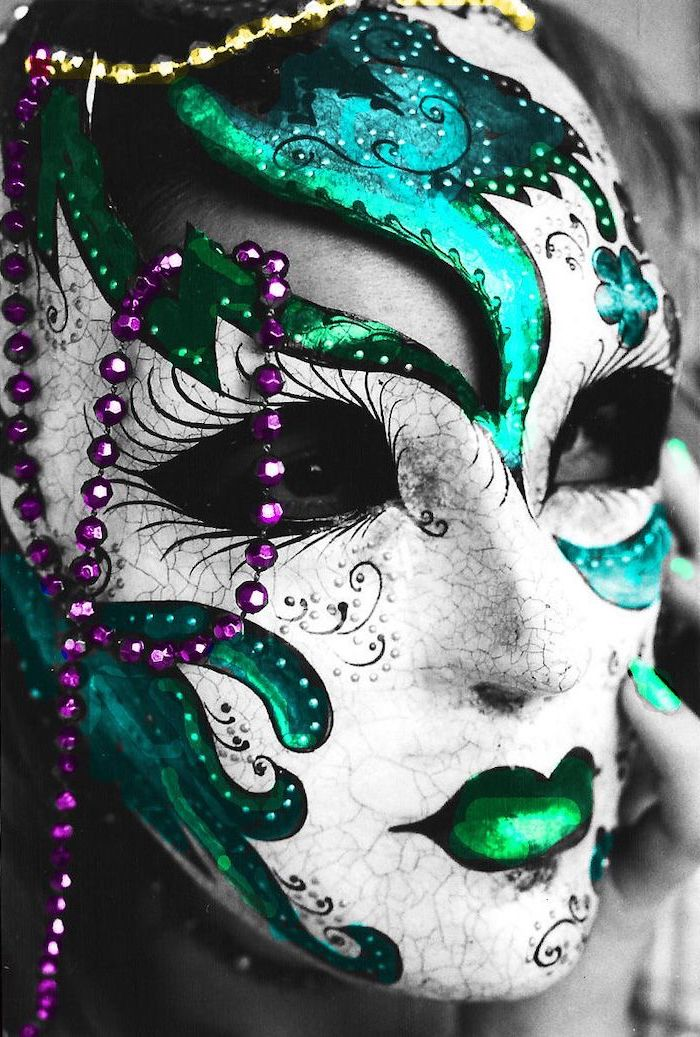 white mask with turquoise decorations, masquerade masks for men, purple and gold beads necklaces around it