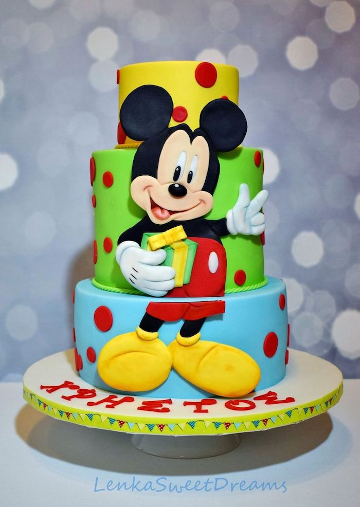 three tier cake, covered with yellow green and blue fondant, mickey mouse cake ideas, placed on white cake stand