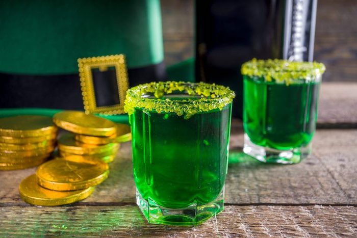 green drink in a glass, yellow sugar around the rim, placed on wooden table, st paddy's day, gold coins around it