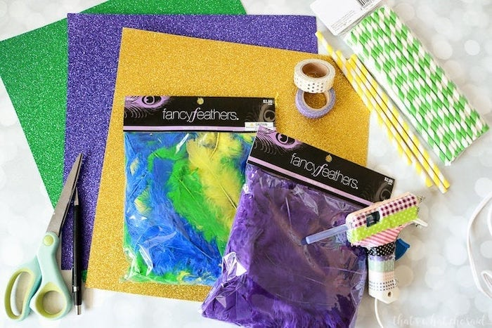 gold purple and green glitter paper, masquerade ball masks, colorful feathers and paper straws, necessary supplies