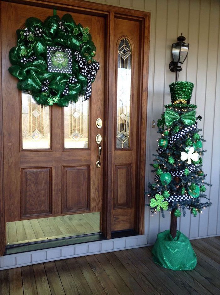 large wooden door, wreath with green tulle, decorated with black and white ribbons, decorated tree on the side, happy st patrick's day