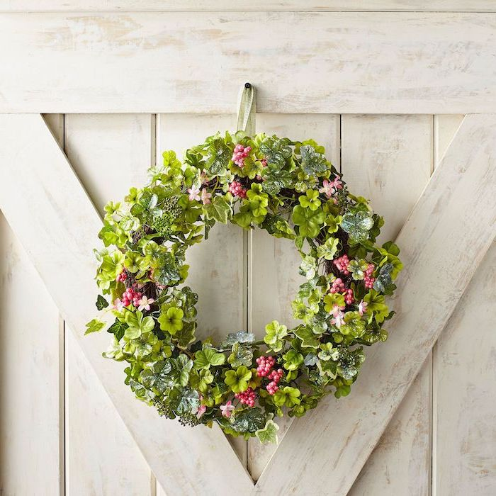 greenery wreath with faux flowers and shamrocks, happy st patrick's day, hanging on white wooden wall