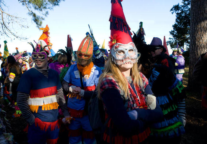 men and women gathered outside, wearing different costumes, male masquerade masks, large hats and masks