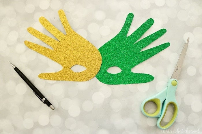 two handprints, made of gold and green glitter paper, masquerade masks for women, connected together