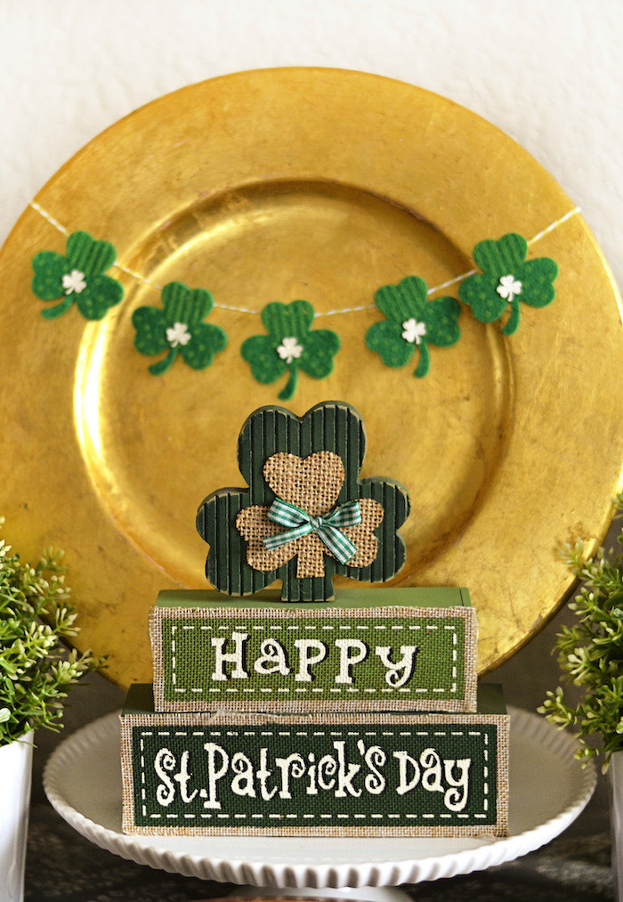 wooden block stacked together, happy st patrick's day, written on them, wooden shamrock on top