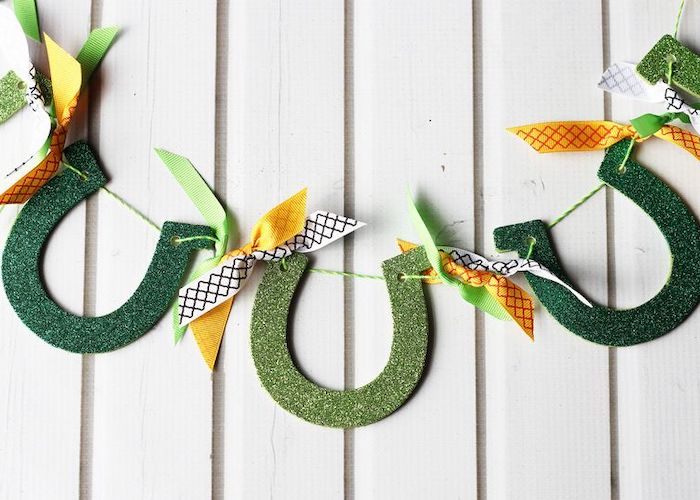 step by step diy tutorial, horseshoe garland made with green glitter, st patrick's day crafts, hanging on white wooden wall