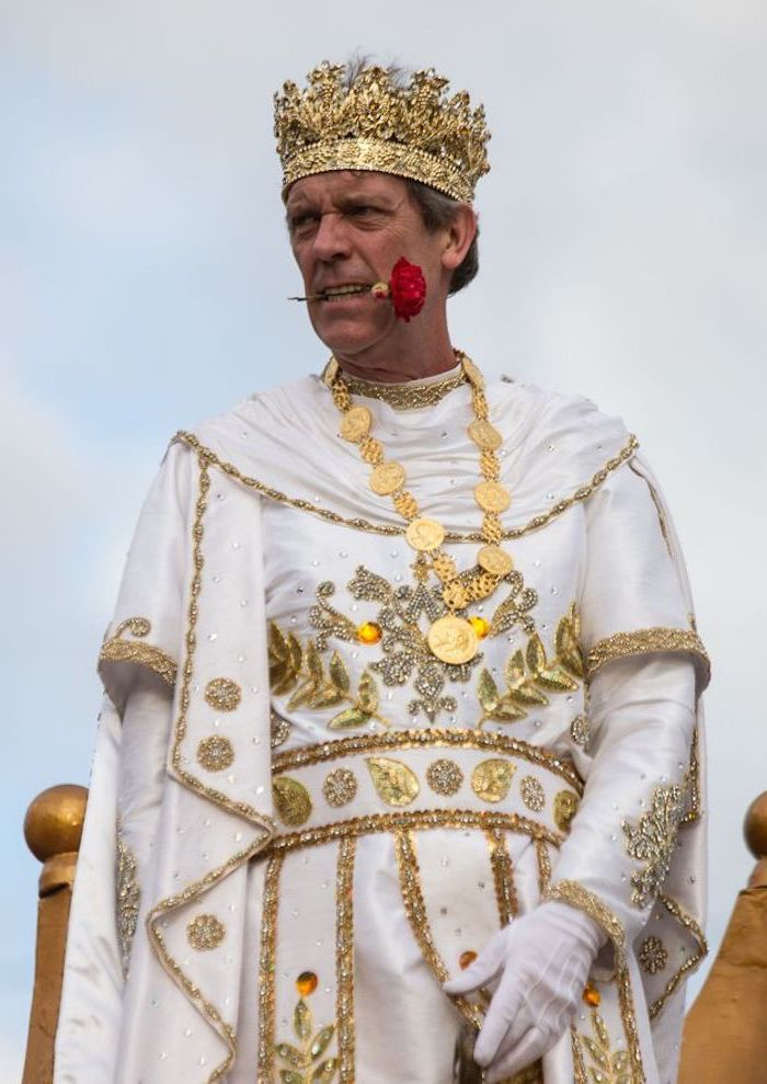 hugh laurie as king bacchus, masquerade masks, wearing white and gold costume, gold crown on his head
