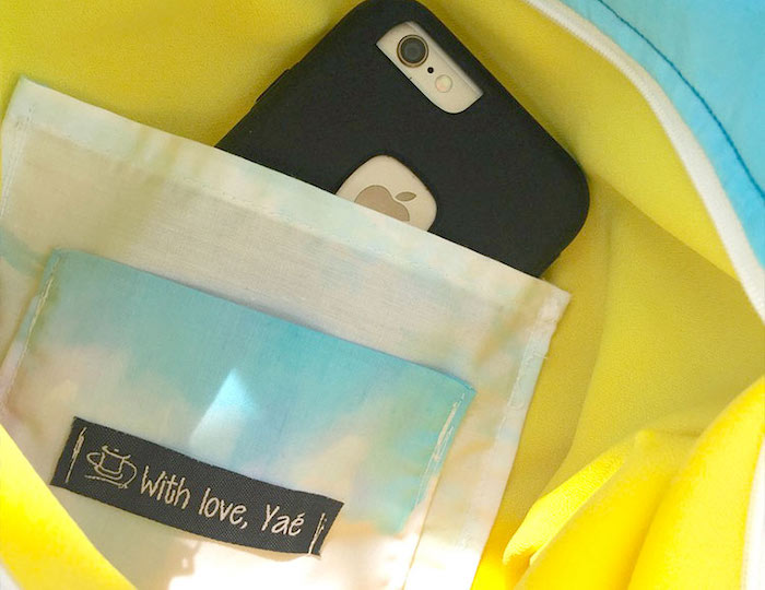 iphone placed inside a jacket pocket, yellow jacket with white pocket, clothing labels, with love yae