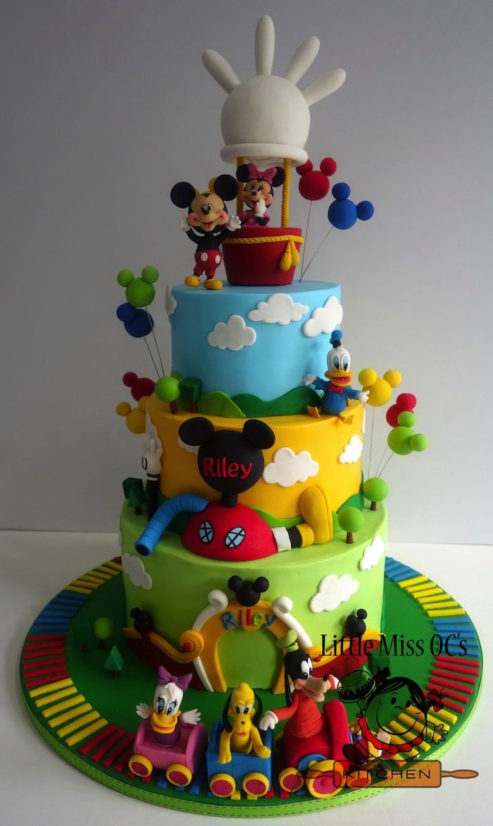 three tier cake, mickey mouse cake ideas, covered with blue yellow and green fondant, disney characters decorations