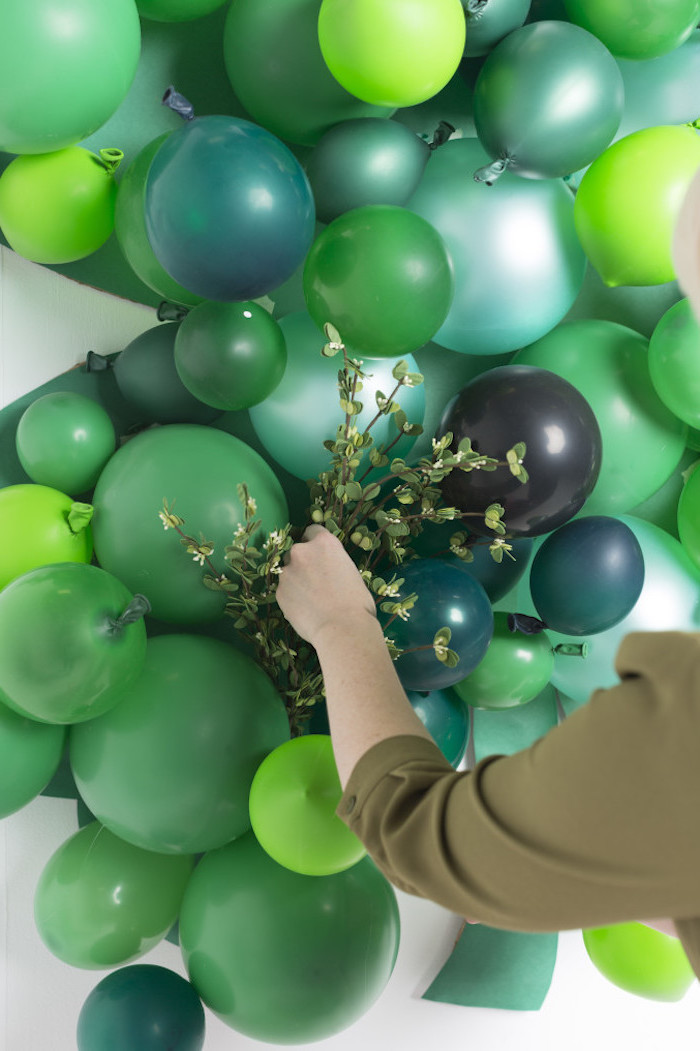 balloons in different shades of grey, arranged together, happy st patrick's day, faux greenery between the balloons