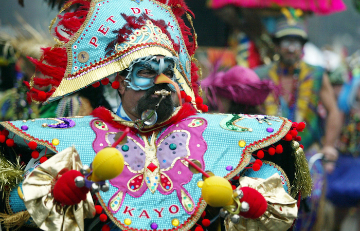masquerade decorations, man dressed in a colorful costume, decorated with red tassels and pom poms