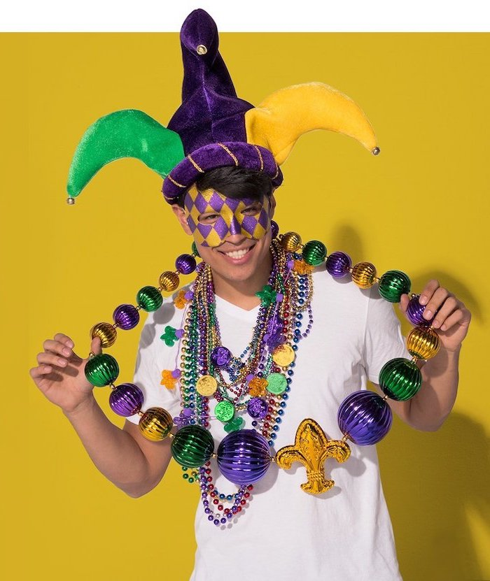 man wearing lots of beads necklaces, masquerade ball masks, purple and gold mask, purple gold and green jester hat